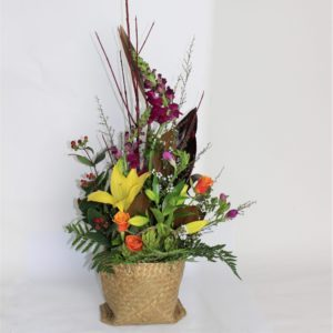 Muriwai Sunset. Tall red branches and flax with manuka, kanuka and magnolia frames this rich arrangement in a kete bag. Featuring yellow lilies, hot pink snapdragon, freesia, orange roses, red and green luecadendron